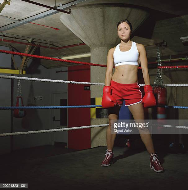 Young female boxer standing in ring with arms down, portrait