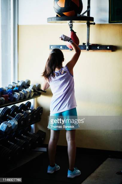 young female boxer warming up on speed bag in boxing gym - boxing shorts stock pictures, royalty-free photos & images