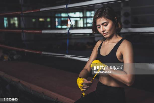 young female boxer wearing strap on wrist. woman in sports clothing preparing for boxing fight or workout. fitness young woman with muscular body preparing for boxing training at gym. - boxing stock pictures, royalty-free photos & images