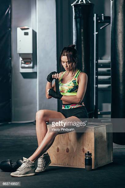 Young female boxer wrapping hand wrap while sitting at gym