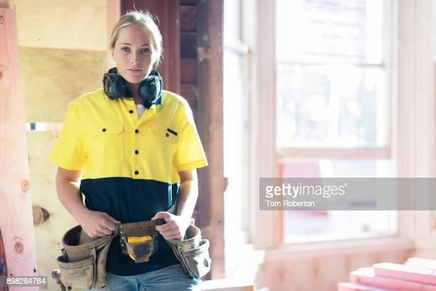 Young female builder on building site