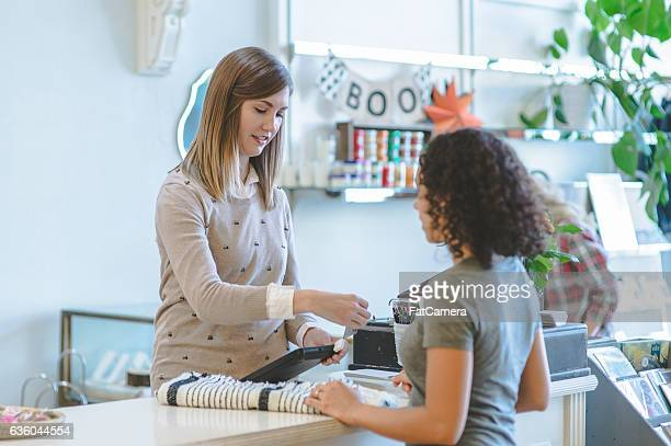 Young female business owner swiping credit card of customer