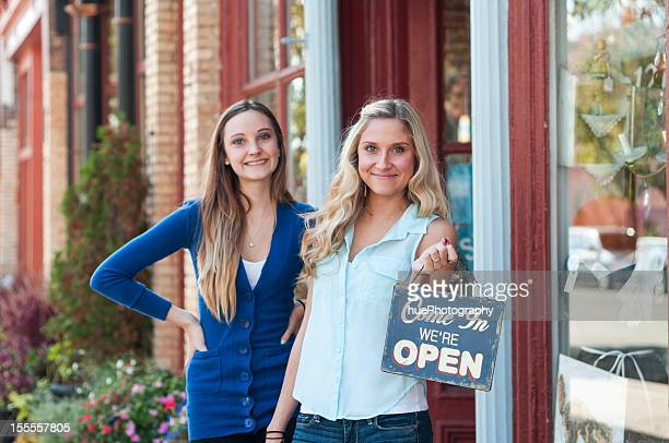 Young female business partners holding an open sign outside