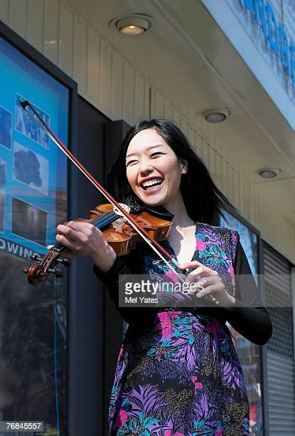 Young female busker playing violin outside cinema, smiling