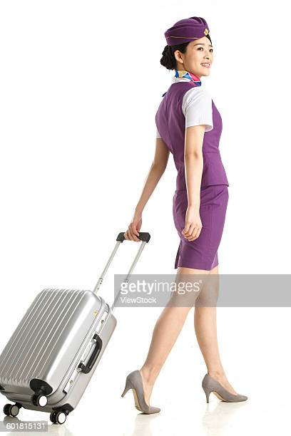 young female cabin crew pulled a wheeled baggage - wheeled luggage stock photos and pictures