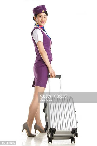 Young female cabin crew pulled a wheeled baggage