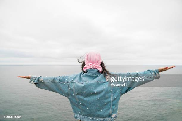 young female cancer survivor with arms outstretched looking at sea against cloudy sky - jacket stock pictures, royalty-free photos & images