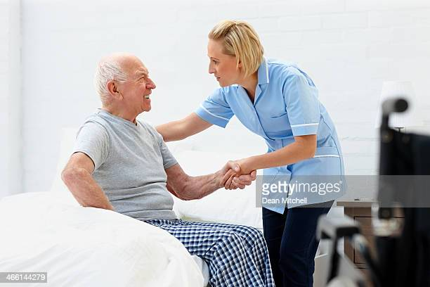 Young female caregiver helping senior man