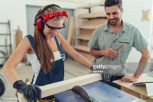 junge weibliche zimmermann holzfällen auf elektrische säge - unterschicht stereotypen stock-fotos und bilder