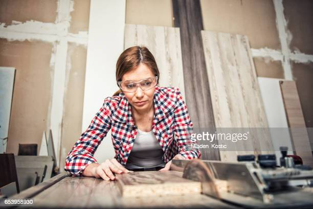 Jonge vrouwelijke timmerman met een cirkelzaag