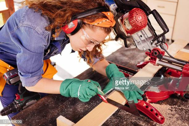 young female carpenter with a miter saw. - mitre stock pictures, royalty-free photos & images