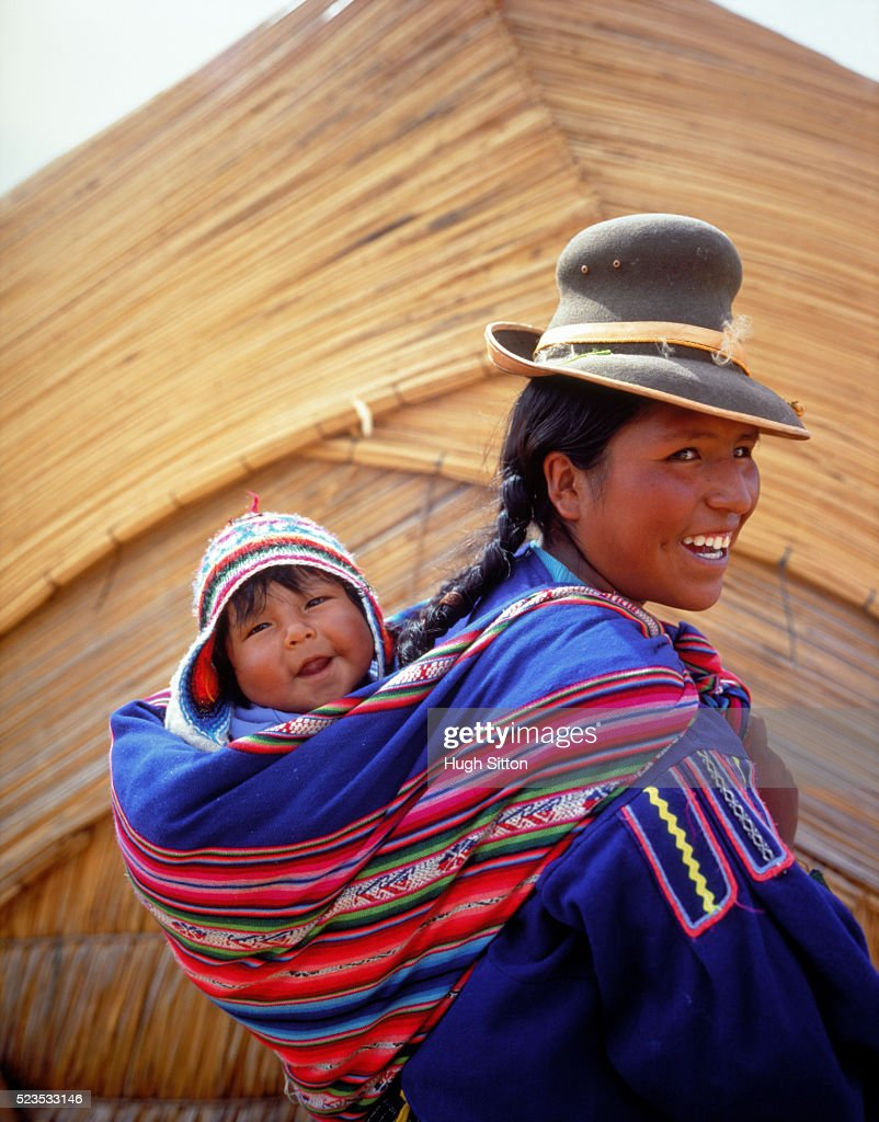 A young female carrying her baby at the body back, Peru : Stock Photo