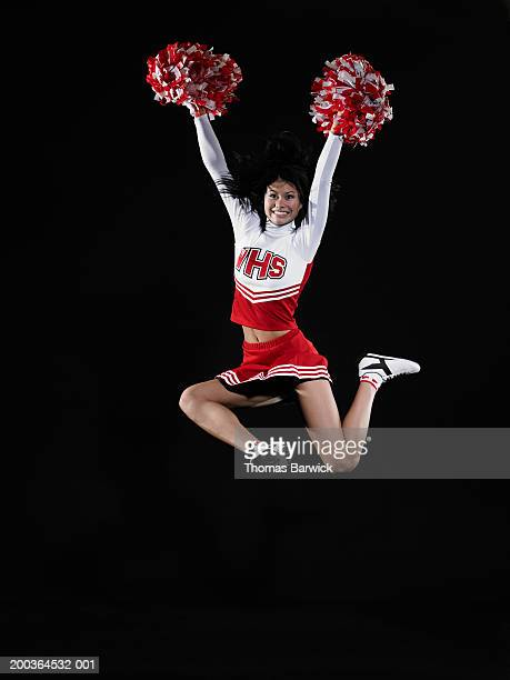 young female cheerleader jumping in midair, arms raised - asian cheerleaders stock photos and pictures
