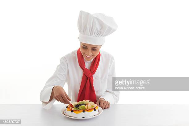 Young female chef decorating fruitcake over white background