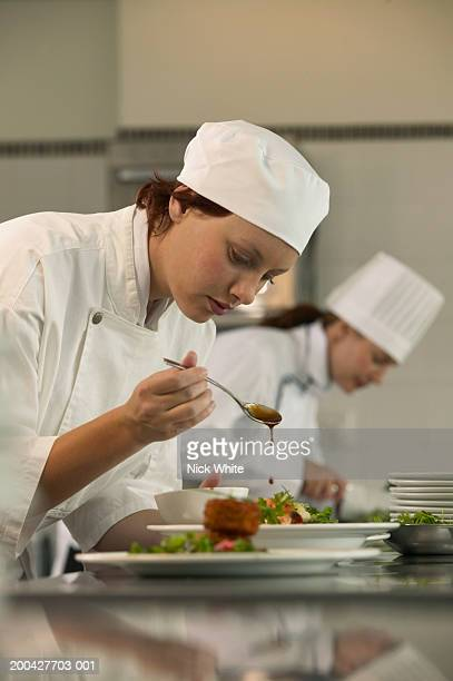 Young female chef preparing food in kitchen, side view, close-up