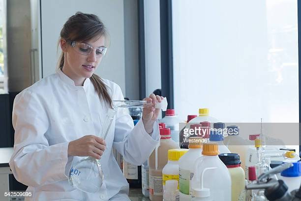 Young female chemist filling liquid in recipient in a chemical laboratory