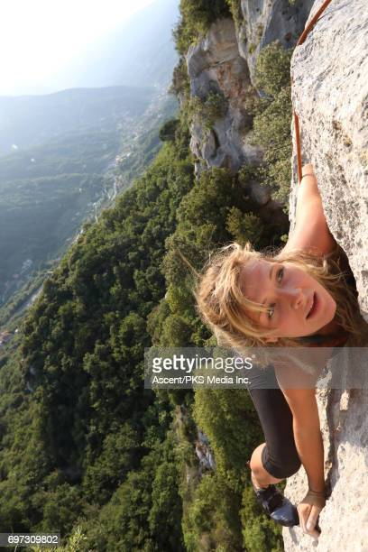 young female climber ascends vertical rock, above valley - leanincollection stock pictures, royalty-free photos & images