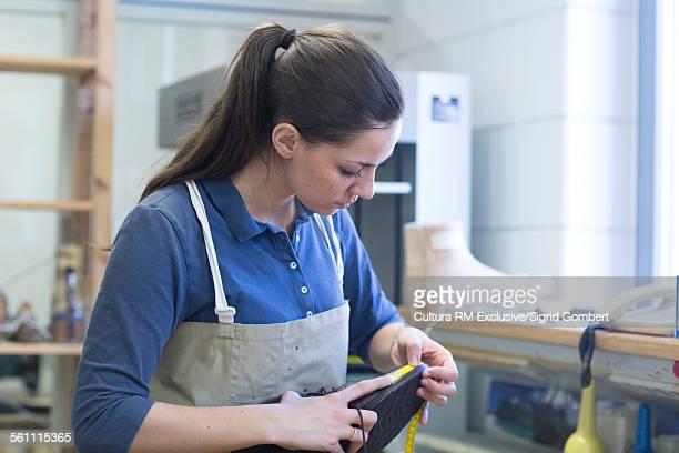 young female cobbler measuring shoe in workshop - sigrid gombert stock-fotos und bilder