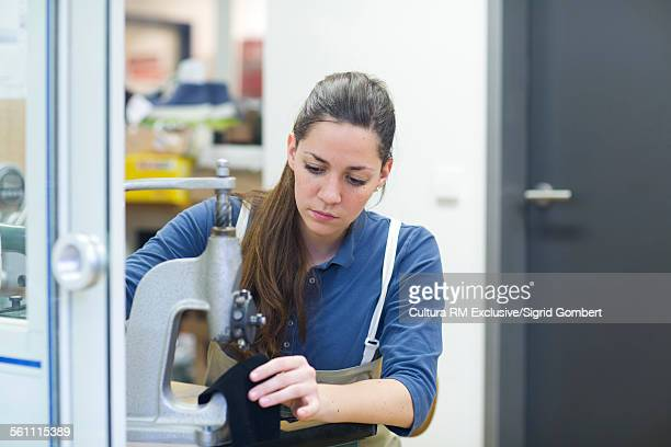 young female cobbler using machine on leather skin in workshop - sigrid gombert stock pictures, royalty-free photos & images