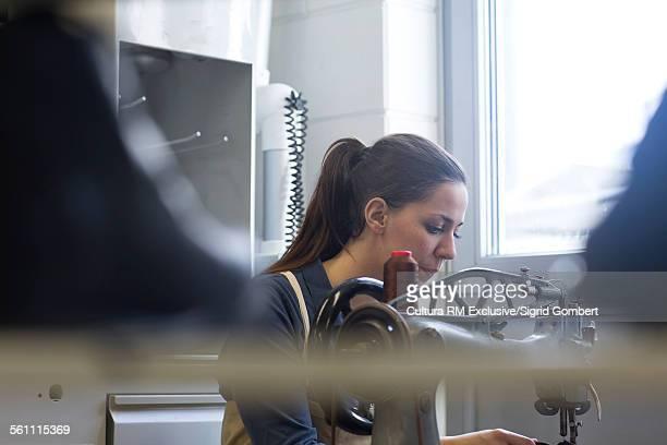 young female cobbler using stitching machine in workshop - sigrid gombert stock-fotos und bilder