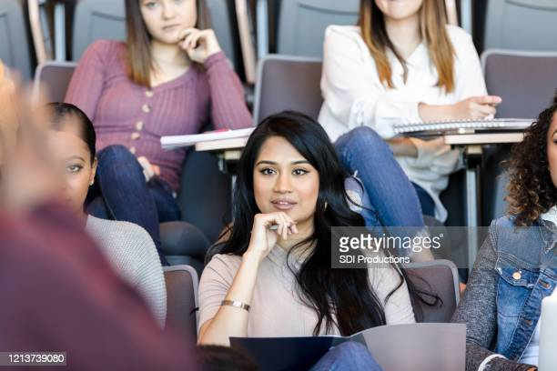 young female college student listens to lecture - community college stock pictures, royalty-free photos & images