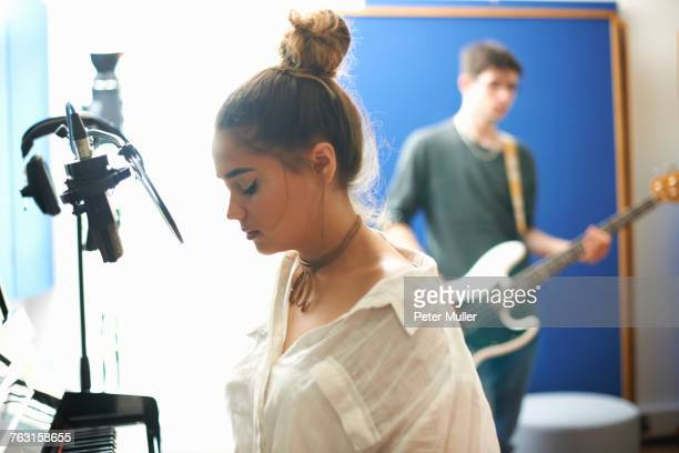 Young female college student preparing to sing in recording studio