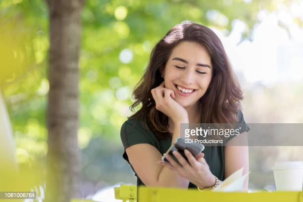 young female college student relaxes on campus with mobile phone - college application stock photos and pictures