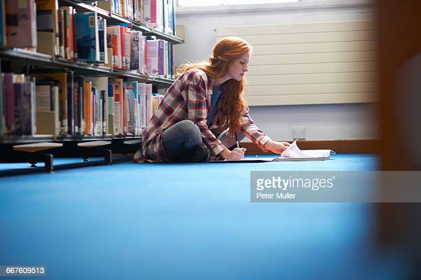 Young female college student writing notes on library floor