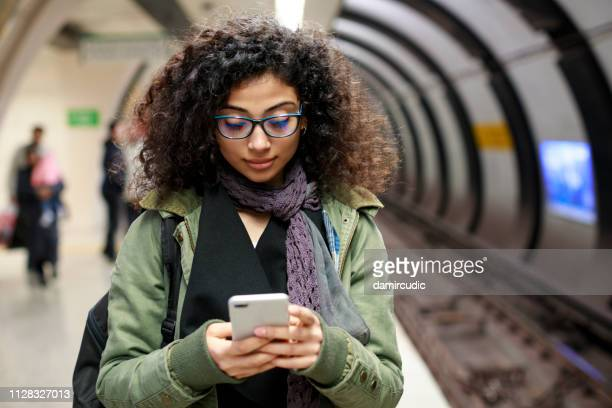 jonge vrouwelijke commuters gebruik mobiele telefoon in het metrostation - tienermeisjes stockfoto's en -beelden