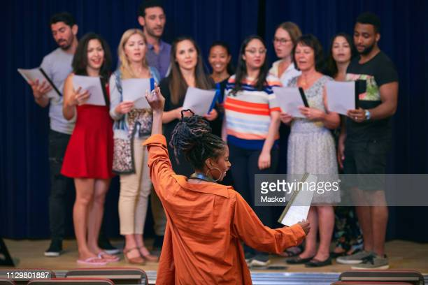 young female conductor directing choir on stage in auditorium - musical conductor stock pictures, royalty-free photos & images