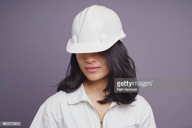 Young female construction worker wearing hardhat against purple background