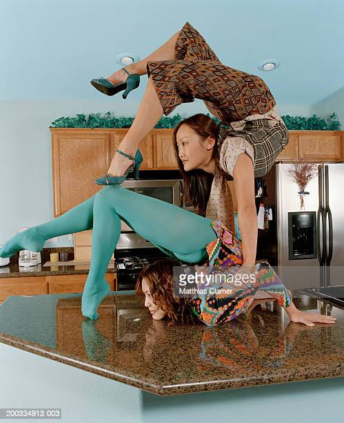 Young female contortionists bending over backwards in kitchen