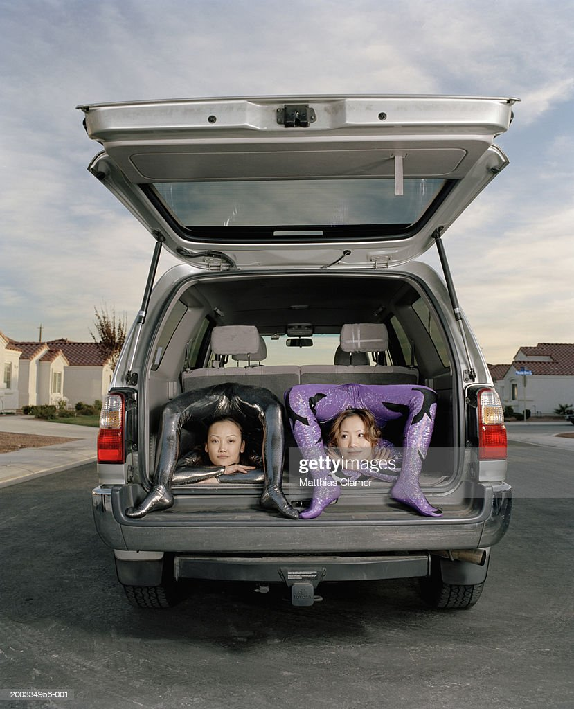 Young female contortionists bending over backwards in vehicle : Stock Photo