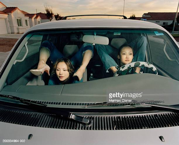 Young female contortionists in car bending legs over shoulders