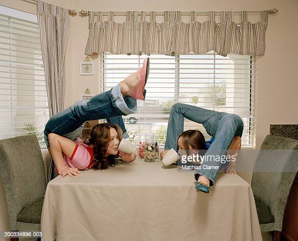 Young female contortionists sipping from mugs on table, side view
