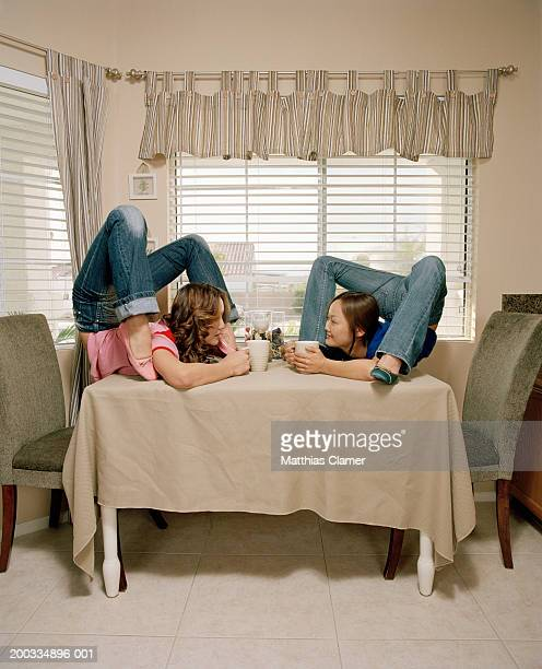 Young female contortionists with mugs on dining table, side view
