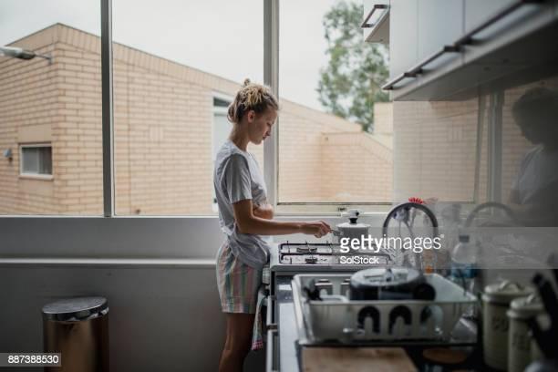 jonge vrouw koken - routine stockfoto's en -beelden