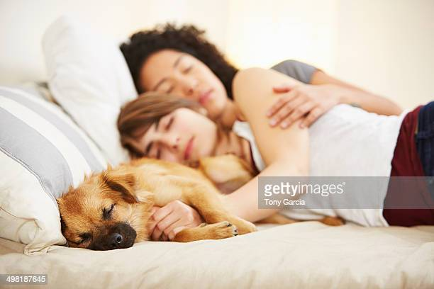 Young female couple and pet dog sleeping on bed