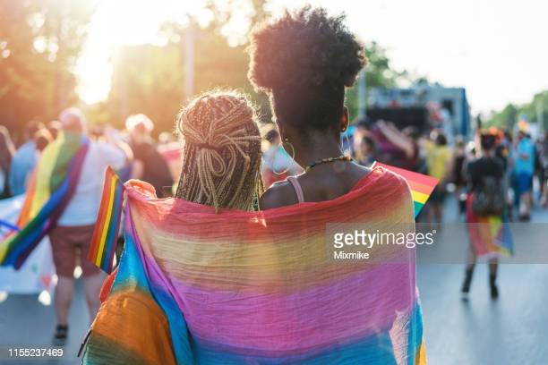 young female couple hugging with rainbow scarf at the pride event - pride stock pictures, royalty-free photos & images