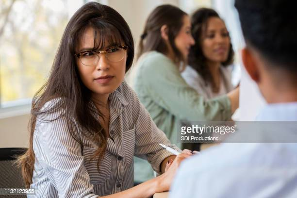 young female creative professional listens to coworker - frowning stock pictures, royalty-free photos & images