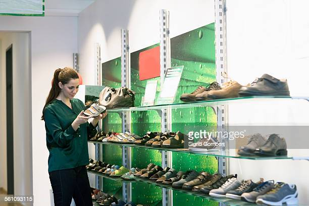 young female customer selecting sandal in shoe shop - sigrid gombert stock pictures, royalty-free photos & images