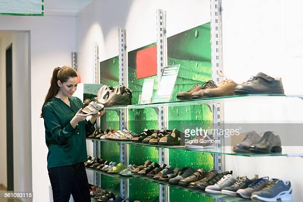 young female customer selecting sandal in shoe shop - sigrid gombert - fotografias e filmes do acervo
