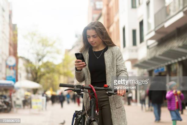young female cyclist looking at smartphone on pedestrian street - sigrid gombert stock pictures, royalty-free photos & images