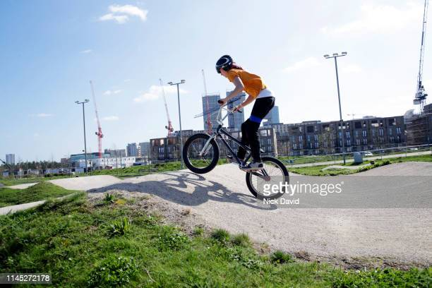 young female cyclist standing on bmx over hump in urban cycling track - bmx track london stock pictures, royalty-free photos & images