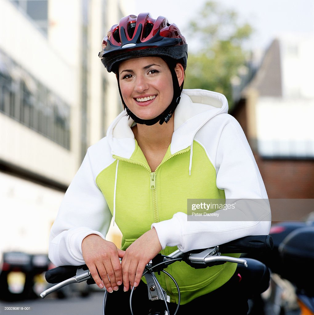 Young female cyclist wearing helmet, smiling, portrait : Bildbanksbilder