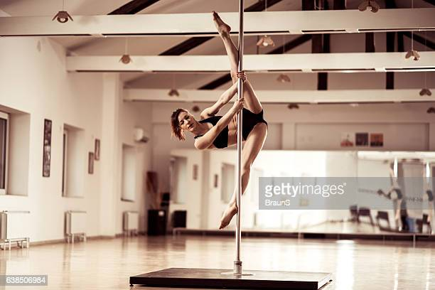 Young female dancer exercising extended frodo on a pole.