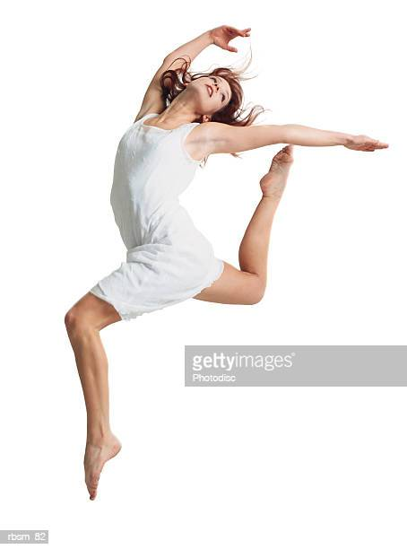 A young female dancer in a white dress runs and leaps forward as she throws her arms and head back