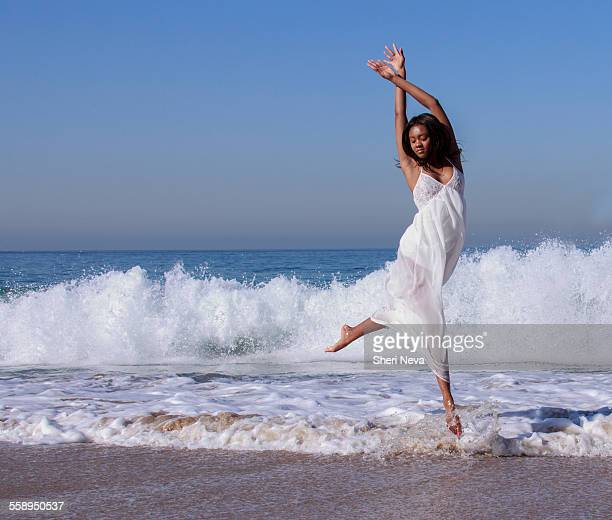 Young female dancer leaping mid air in ocean waves
