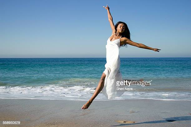 young female dancer leaping mid air on beach - 白い服 ストックフォトと画像