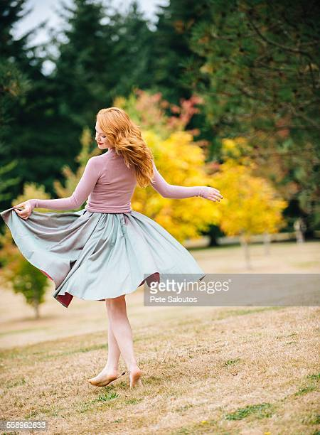 Young female dancer twirling and lifting skirt in park